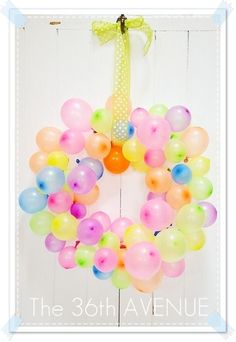 Balloon wreath for a birthday party. I like the idea of using it simply as a party decoration, but here it's used for a dart party game.