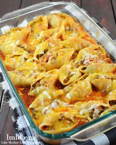 Mexican Stuffed Shells - filled with a ground beef and cream cheese mixture, cooked in a bath of enchilada sauce and salsa topped with cheddar cheese. #lmldfood