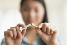 woman breaking cigarette in half - JGI/Tom Grill/Blend Images/Getty Images
