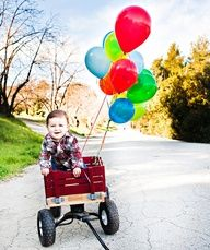 Colorful balloons and a little red wagon are the prefect props for a birthday photo shoot for a little boy! a Its all about composition! For a little girl, pink balloons and a stylish chair (a Salvation Army find for $10) set in an unconventional setting make for a memorable first birthday photo.
