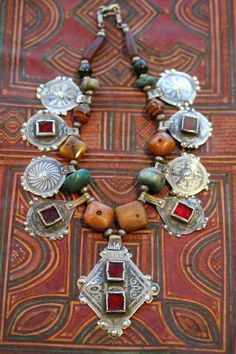 Fossil amber, amazonite, niello with red glass inserts, silver, old Ida Oberstein faceted carnelian, old Bohemian wound glass beads that replicate agate, old bone prayer beads studded with silver.