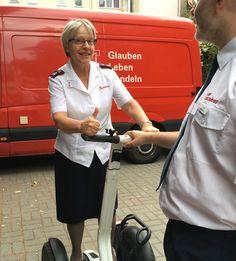 Die Leiterin der Heilsarmee in Deutschland, Kommandeurin Marie Willermark, zusammen mit dem Leiter der Heilsarmee in Leipzig, bei einer Probefahrt auf einem Segway.