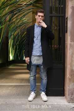 Distressing denim | Wear a blue button up shirt under an overcoat, then rock some distressed denim jeans and a pair of white trainers to complete the sharp but simple outfit. | Shop men's clothing at The Idle Man