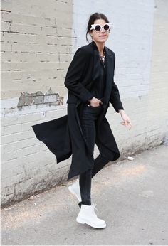 Man Repeller in all black, trench coat, shades, white tims