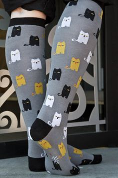 Yellow, white and black cats solemnly stare from these socks . . .wait! The black cat is winking! What are they up to?
