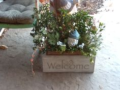 Winter porch. Whiskey box with clippings from the yard and a gnome. Put my welcome sign in front. Looks cute.