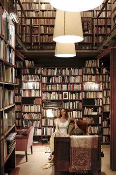 La escritora Nuria Amat sentada en la cama de su biblioteca, rodeada de más de 10.000 libros.