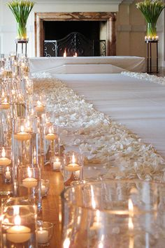 Floating candles light the aisle. Michael George Flowers