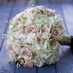 The bridal bouquet will be a small, round clutch bouquet of white hydrangeas, shades of pink ranunculus, blush pink rose, and white lily of the valley wrapped all the way to the ends of the stems in ivory satin ribbon with sparkly brooch accent.
