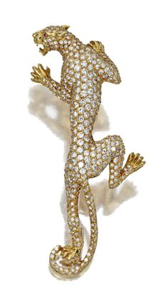 DIAMOND PANTHER PENDANT-BROOCH, CARRERA & CARRERA.    Modeled as a fierce stalking panther, pavé-set throughout with small round diamonds, the eyes set with small round rubies, mounted in 18 karat gold, signed Carrera y Carrera, numbered 37130.