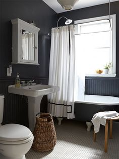 Here, gray-black takes a bathroom from quaint to chic, never crossing into stark territory thanks to the addition of natural wood accents.
