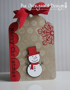 handmade Christmas tag ... kraft base with red and white ... cute snowman ... luv the depth made by stamping and then stamping and cutting out without twig arms to put on top of the original ... luv red and kraft together ... Hero Arts