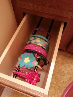 Two tension rods in drawer for head band storage- could do this in a narrow bookcase too