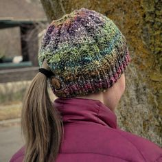 knit the brim flat(button hole?)  and up through the ponytail area, then join in the round for the crown, seaweed pattern is just knits and purls in a pattern that shifts