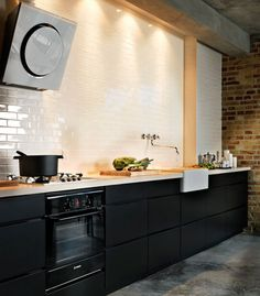 Loft-style kitchen. Modern but cool. Like the subway tile and exposed brick.