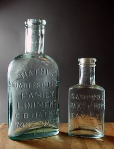 Mathis' Family Liniment - 25cent size (on left) and sample size (on right). LEFT: aqua, tooled double ring lip, oval, 4 1/4in (108mm) tall. Embossing: MATHIS' / QUARTER DOLLAR / FAMILY / LINIMENT / C.B. MATHIS / TOMS RIVER / N.J. (across back). RIGHT: aqua, tooled double ring lip, oval, 2 7/8in (73mm) tall. Embossing: SAMPLE / MATHIS' / FAMILY / LINIMENT (across front), C.B. MATHIS / TOMS RIVER / N.J. (across back) No vent hole bumps on either... c1880.