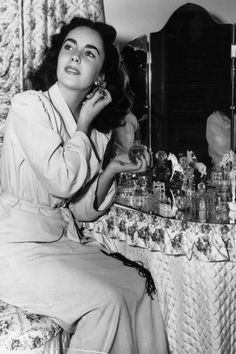 Liz lounges in a cozy robe as she gets ready at her dressing table, which features an assortment of perfume bottles and glass knick-knacks.   - MarieClaire.com