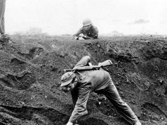 A U.S. Marine approaches a Japanese soldier on Iwo Jima, Japan, on March 16, 1945 - AP Photo