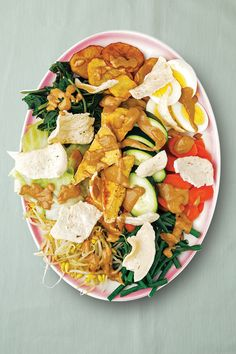 On the streets of Jakarta and elsewhere in Indonesia, some vendors' pushcarts are essentially mobile salad bars, where bespoke vegetarian compositions of greens, sprouts, shredded cabbage, fried potatoes and tofu, hard-cooked eggs, shrimp chips, and more are dressed in a spicy and aromatic peanut sauce. This salad lends itself to creativity; nearly any combination of raw and cooked vegetables, along with rice or thin noodles, if you like, can be used.