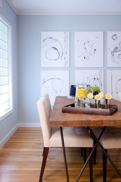 Pale blue dining room walls and beautiful wood floors.