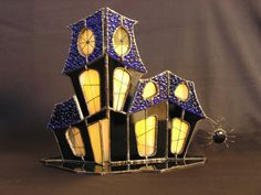 A beautifully unique, handmade, 3D black stained glass haunted house with 42 hand cut pieces of stained glass. Layered blue textured glass for the
