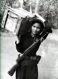 A female Viet Cong combatant carrying supplies and a captured U.S. M1 carbine