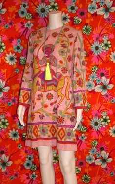 """Amazing signature print 1960s mini shift by Eloise Curtis for Happenstance. Design centers around Hindu god Krishna, in neon pinks, orange and greens. The ultimate psychedelic blacklight dress! Rear nylon zipper, and belled sleeves. We have paired with a modern necklace (not included) In very good condition Measures: 36"""" Bust, 36"""" Length, 21"""" Sleeve"""