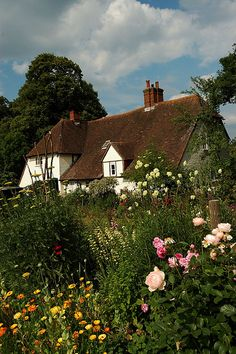 Manor Farm in Hampshire. I can't decide if I like the flowers, the perfect puffy clouds in the blue sky, or the lovely thatched roof more!!