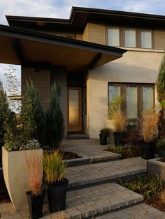This statement entryway was designed with the architectural lines of the home in mind. The landscaping creates a cascade of stone levels leading to the front door, complete with large over-sized planters and shrubs.