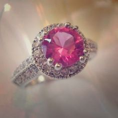 Gorgeous 2CT Crown Set Pink CZ Ring Material: White Gold Plated Color: Pink Condition: New Size: 7.   This gorgeous ring features a 2Ct Pink CZ stone surrounded by multifaceted clear cz stones all set to perfection in an 18K white gold plated setting. Jewelry Rings