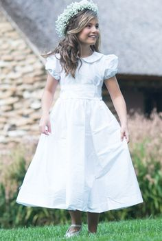 Audrey is an iconic 100% Dupioni Silk White dress with a scalloped collar, covered buttons and silk sash tied bow. Includes built in slip with tulle underskirt for fullness. The white Dupioni Silk has