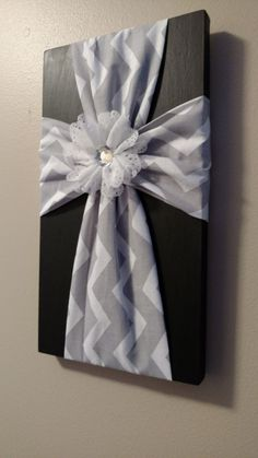 Gray and White Chevron cross adorned with white rhinestone flower. Great wall hanging for any decor or it makes a great gift too! The finished product has a wall hanger attached to the back for easy wall mounting. This plaque can sit on a shelf or comes ready to hang on the wall.