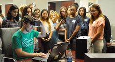 A group of girls watch a virtual reality demonstration during Girls Who Code…