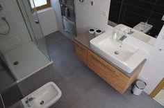 Koupelna se sprchovým koutem v příjemných neutrálních barvách. Šedou dlažbu a bílé obklady skvěle doplňují dřevěný nábytek a bílá sanita - ProŽeny.cz