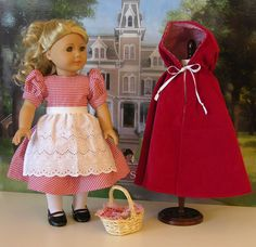 """Little Red Riding Hood costume by cupcakecutiepie -  *Pretty red gingham print dress with puff sleeves and bias hemline border. Dress fastens with three buttons in back.    *Darling half apron in white eyelet that self ties in back.    *Beautiful red corduroy cape is fully lined in coordinating red gingham cotton print. Hooded and ties at the neck with a white ribbon.    Bonus Gifts: White tights and black ballet flats. Picnic basket with red gingham print """"bread cloth""""."""