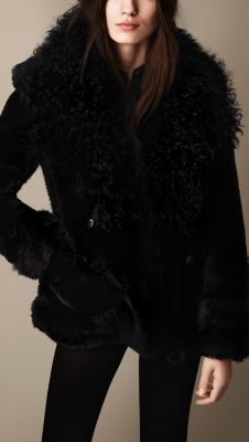 An oversize reverse shearling pea coat. Made from a patchwork of contrasting textures, the design features a collar of curly shearling and a soft shaved shearling body, with contrast detail at the hem and cuffs. An oversize martingale defines the silhouette while referencing heritage designs.
