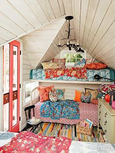 Maximize angled dormer ceilings by turning a small space into lofted bunks. Eclectic Bohemian style is ideal for mismatched bedding and furniture. Whitewashed plank walls let the fun patterns and bright colors be the focus./