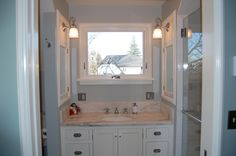 Small Bathroom Vanity With White Cabinet Under The Square Window And Round Sink