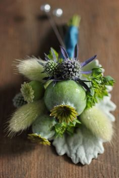 Poppy pod, bunny tail grass, eryngium, and bupleurum on dusty miller - boutonniere