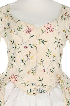 Detail front, open robe, England, 1770s. Cream linen, embroidered in silks with meandering stylised honey-suckle trails.