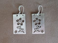 Large Rectangular Cherry Blossom Earrings.  These earrings are light and airy and sparkle with a polished finish as they swing from the ears. They are inspired by Japanese kimono fabric designs.  They are made of sterling silver, flat, rectangular shapes. They are pierced with a design of cherry blossoms. The ear wires are also made of sterling silver.
