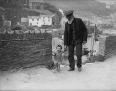 Elderly fisherman Thomas Perry guides his young friend along a stony path on the Cornwall coast at Polperro. 1933.