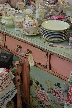 Pink drawers and frame, mint green floral top and doors and crystal pulls.