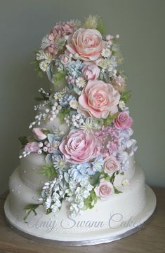 Amy Swann Cakes - Sweet wedding cake with a broad cascade of flowers, roses being the largest, cascading down the cake. lovely.