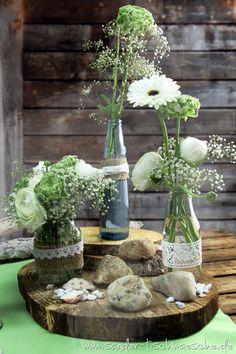 Blumendeko in alten Flaschen mit Spitze und Jute dekoriert - auf Baumscheibe. DIY Centerpiece