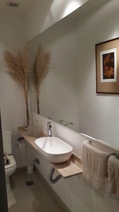 Toilette de recepción diseñado en un ambiente muy angosto, pero largo. Muchos espejos - Cuadros que se reflejan y objetos de decoración en la mesada de mármol con amplia bacha ovalada.