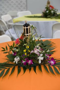 Hawaiian themed wedding reception. Centerpieces and mini tiki torches were lit. Table cloths were all different colors #wedding