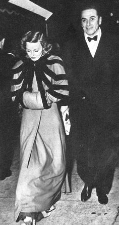 """Margaret Sullavan and husband Leland Hayward at the Gone With The Wind premier in Hollywood, 1939. She is wearing """"a broadcloth coat with [a] quaint elbow caplet and baby pillow muff–all banded in sealskin."""""""