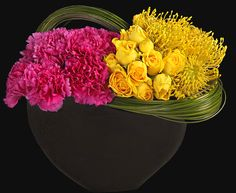 MOTHER'S MÉLANGE by Ovando    carnations, roses, pincushion protea, bear grass in black bowl.