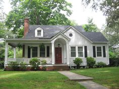 Lovely cottage house with a wrap-around porch and large stately trees.